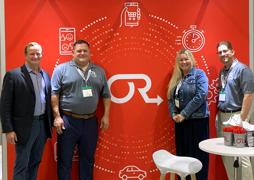 OneRail's Bill and Lisa Catania and group in front of Booth 507